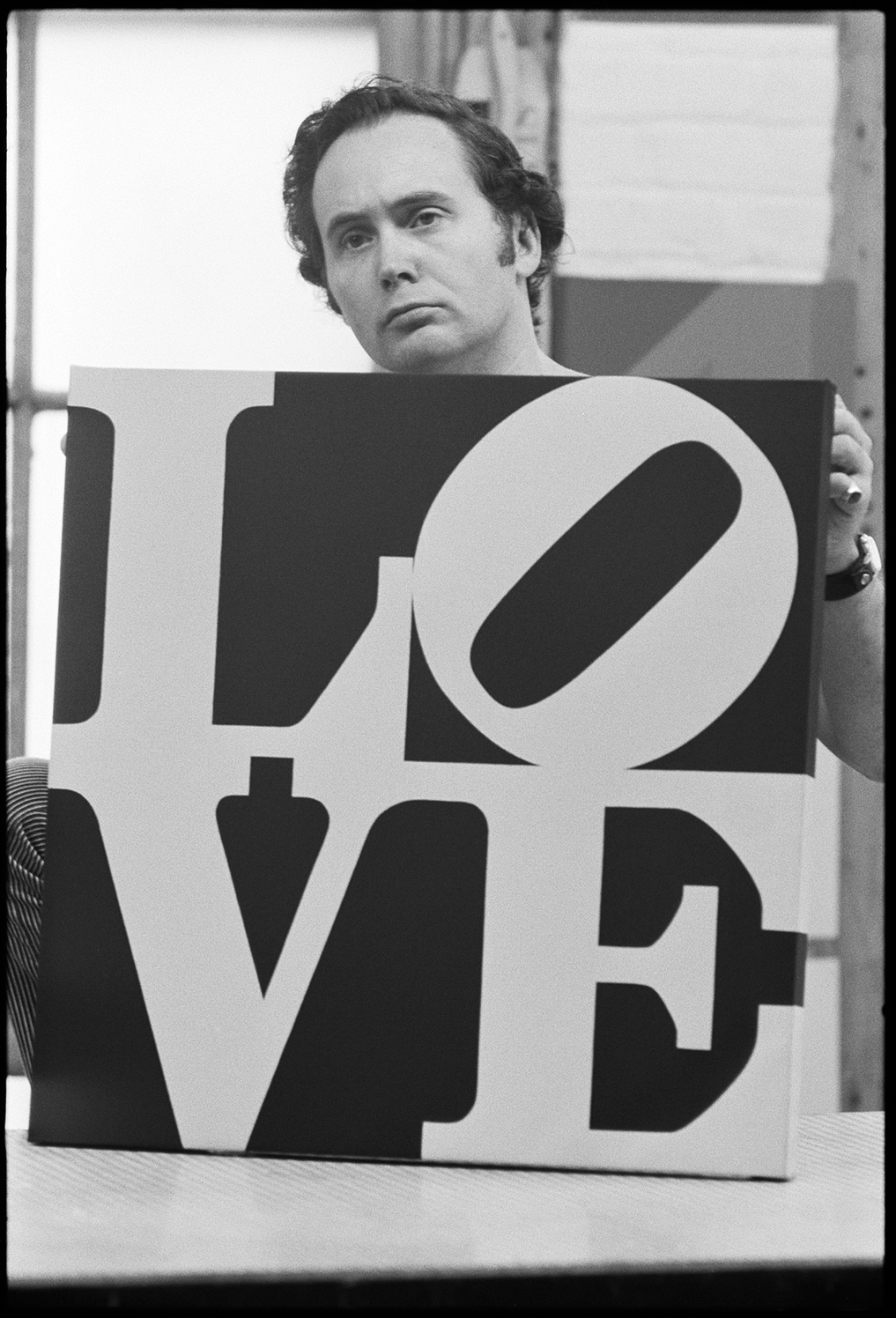 © William John Kennedy, Robert Indiana holding his Love painting, 1964 Courtesy of KIWI Arts Group